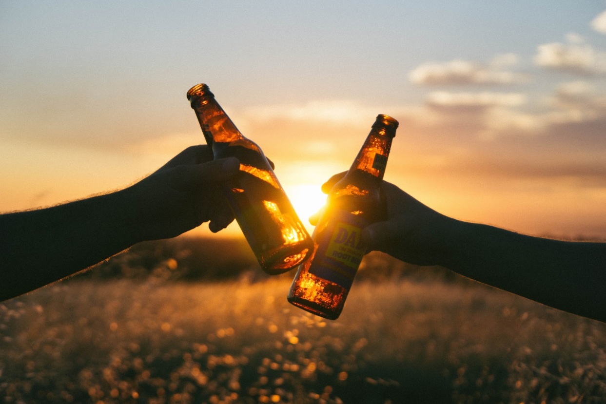 toasting with beer bottles with sunset backdrop