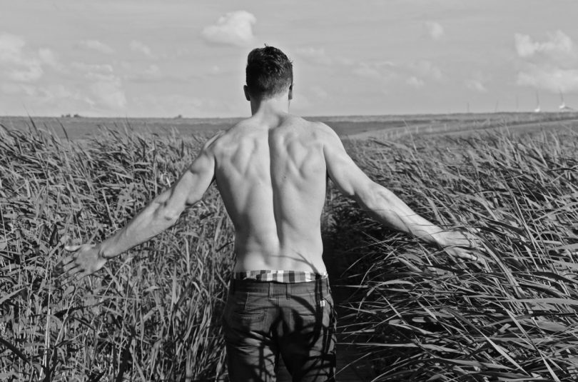 man with sexy muscular back walking through meadow
