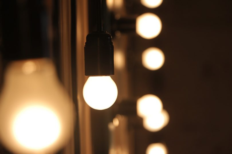 row of light bulbs with one bulb in focus
